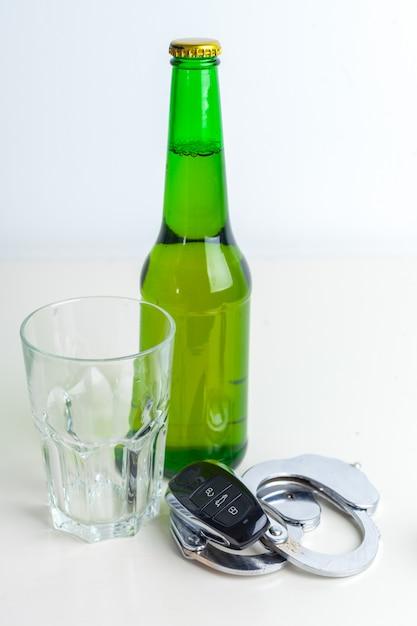 Conceito de condução bêbado - cerveja, chaves e algemas Foto Premium