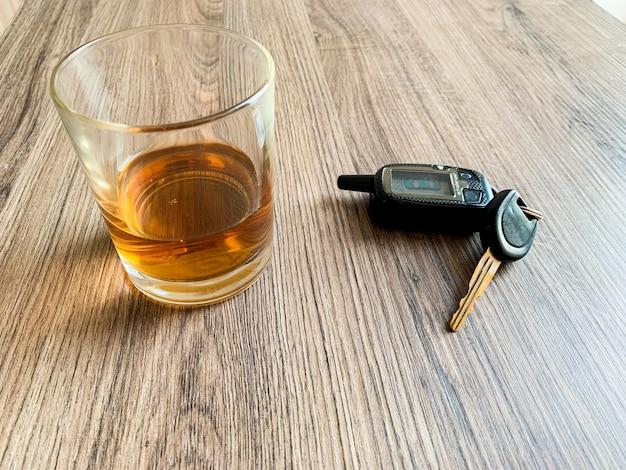 Conceito de condução bêbado. vidro com uísque e chave do carro em cima da mesa. Foto Premium