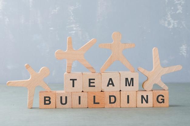 Conceito de construção de equipes com blocos de madeira, figuras humanas de madeira na vista lateral. Foto gratuita
