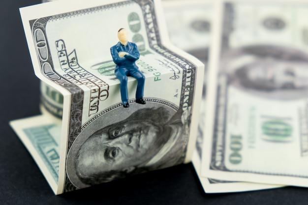 Conceito de corretor financeiro. homem do brinquedo que senta-se em uma nota de banco dos dólares americanos. Foto Premium
