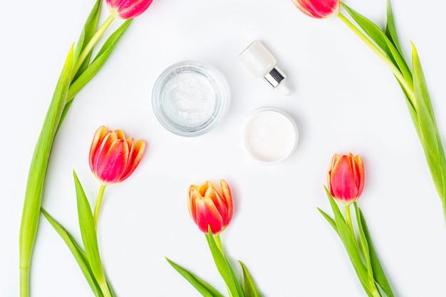 Conceito de cosméticos caseiros orgânicos naturais. cuidados com a pele, remédios e produtos de beleza: recipientes com creme e soro entre flores de tulipa vermelha de primavera em fundo branco. postura plana, cópia espaço para texto Foto Premium