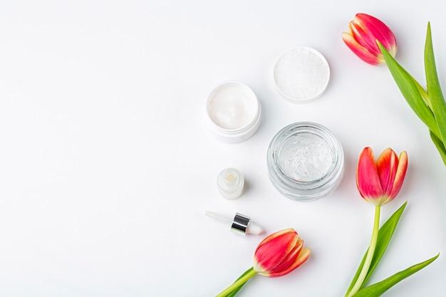 Conceito de cosméticos caseiros orgânicos naturais. cuidados com a pele, remédios e produtos de beleza: recipientes com creme e soro entre flores de tulipa vermelha primavera no fundo branco Foto Premium
