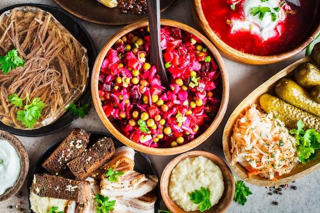 Conceito de cozinha tradicional russa. borsch, gelatina de carne, banha de porco, crepes, vinagrete de salada e chucrute, vista superior, fundo cinza. Foto Premium