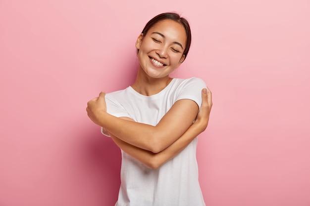 Conceito de cuidado e ternura. mulher asiática morena positiva alegre se abraça suavemente, inclina a cabeça e sorri feliz, mantém os olhos fechados de prazer, tem clima romântico, vestida com roupa casual Foto gratuita