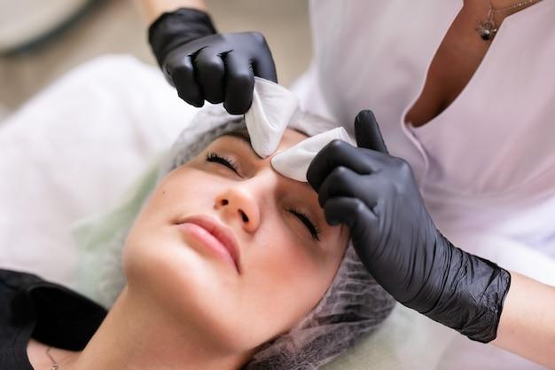 Conceito de cuidados com a pele. uma mulher em um salão de beleza durante um tratamento de cuidados com a pele facial. Foto Premium