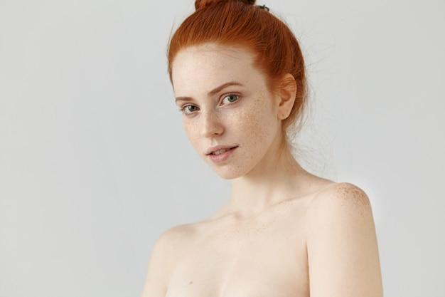 Conceito de cuidados de pessoas, juventude, beleza e pele. retrato de mulher ruiva jovem bonita posando de topless olhando com sorriso misterioso sutil, tendo sardas em todo o rosto e ombros Foto gratuita