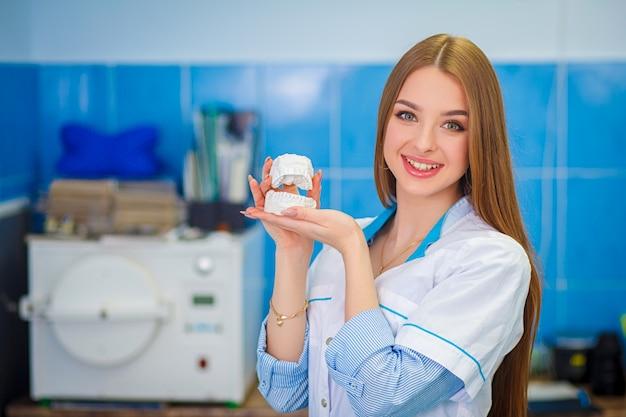 Conceito de cuidados de saúde. próteses dentárias. menina bonita em um jaleco branco segurando modelos de gesso dentais. Foto Premium