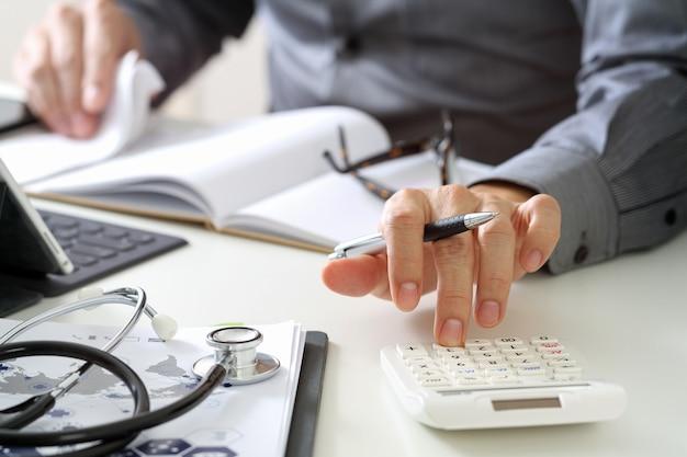 Conceito de custos e taxas de cuidados de saúde. a mão do doutor esperto usou uma calculadora para custos médicos no hospital. Foto Premium