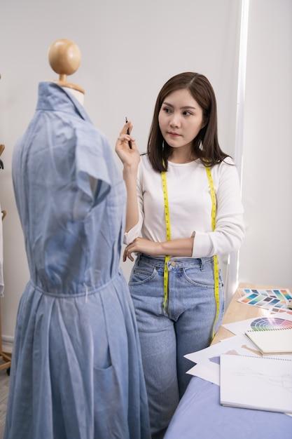 Conceito de designer. a costureira está projetando um vestido de noite no quarto Foto Premium