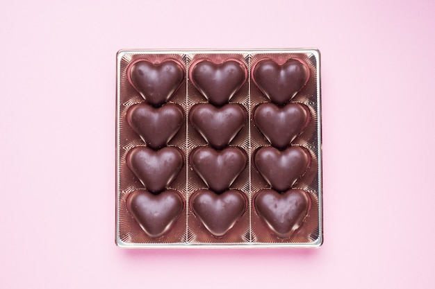 Conceito de dia dos namorados. bombons de chocolate, corações em um fundo rosa Foto Premium