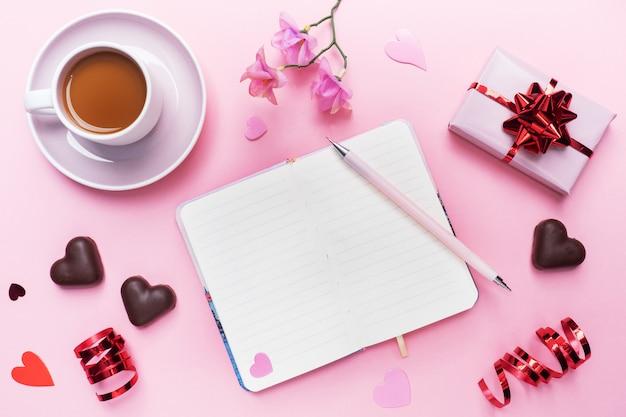 Conceito de dia dos namorados. bombons de chocolate e café, corações em um fundo rosa. espaço de cópia plana leigos. cartão e presente. Foto Premium