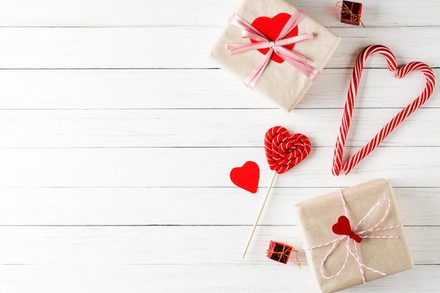 Conceito de dia dos namorados. coração em forma de doces e caixas de presente em branco de madeira Foto Premium