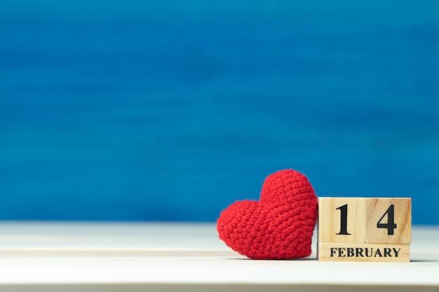 Conceito de dia dos namorados. mão faz fio coração vermelho ao lado do calendário bloco de madeira definido no dia dos namorados 14 de fevereiro Foto Premium