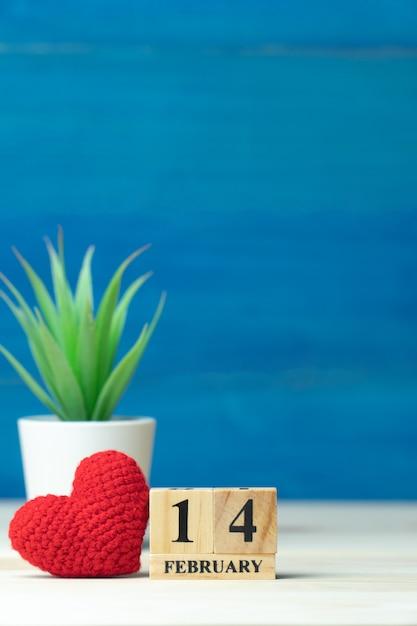 Conceito de dia dos namorados. mão faz fio coração vermelho ao lado do calendário de bloco de madeira Foto Premium