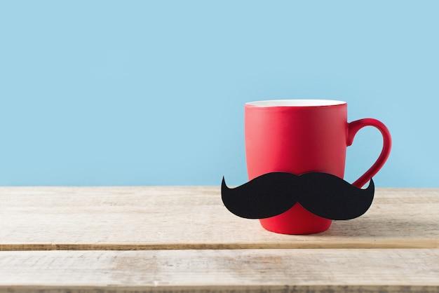 Conceito de dia dos pais com copo vermelho e bigode em fundo azul Foto Premium