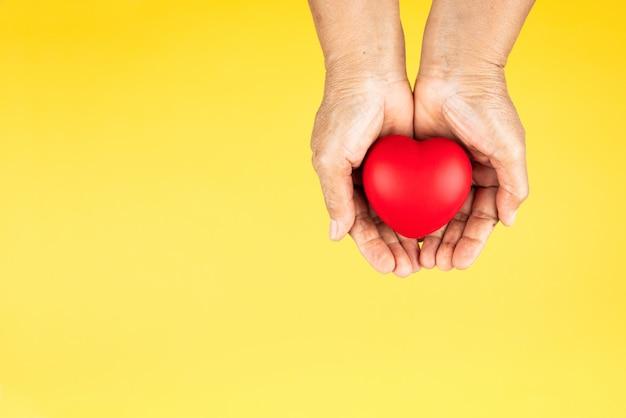 Conceito de dia mundial da saúde seguro médico de saúde com coração vermelho nas mãos da mulher sênior Foto Premium