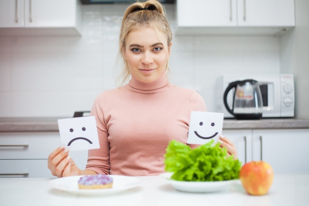 Conceito de dieta, mulher jovem e bonita escolhendo entre alimentos saudáveis e junk food Foto Premium
