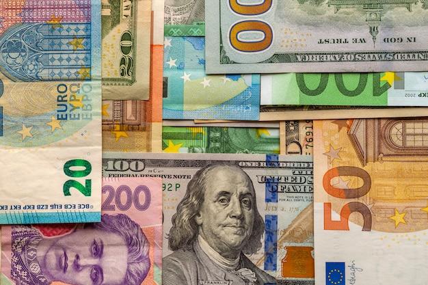 Conceito de dinheiro e finanças. nova nota de cem dólares em fundo abstrato colorido de notas de moeda nacional ucraniana, americana e euro. Foto Premium