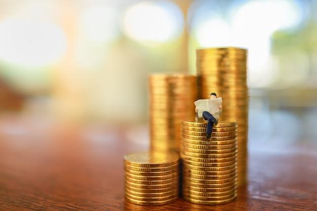 Conceito de dinheiro, negócios, economia e planejamento. feche acima da figura em miniatura perople do homem de negócios que senta e que lê um jornal na pilha de moedas de ouro na tabela de madeira com espaço da cópia. Foto Premium