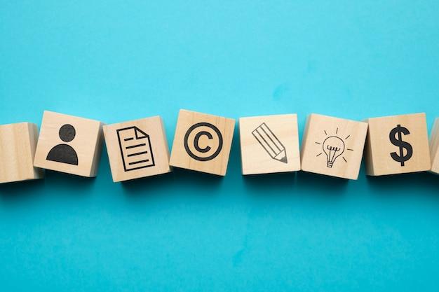 Conceito de direitos autorais com ícones em blocos de madeira. Foto Premium