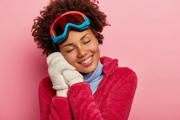 Conceito de diversão, recreação e estilo de vida de inverno. mulher de pele escura usa óculos de snowboard apoiados em ambas as mãos e luvas brancas, lembra-se do momento agradável das férias Foto gratuita