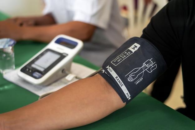 Conceito de doação de sangue. levando a pressão arterial do paciente Foto Premium
