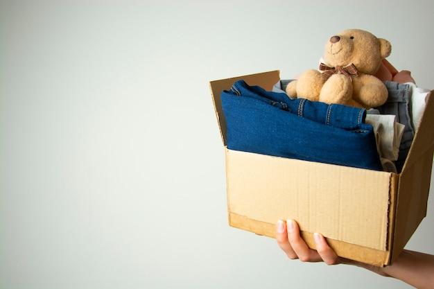 Conceito de doação. mãos segurando doar caixa com roupas. copie o espaço. Foto Premium