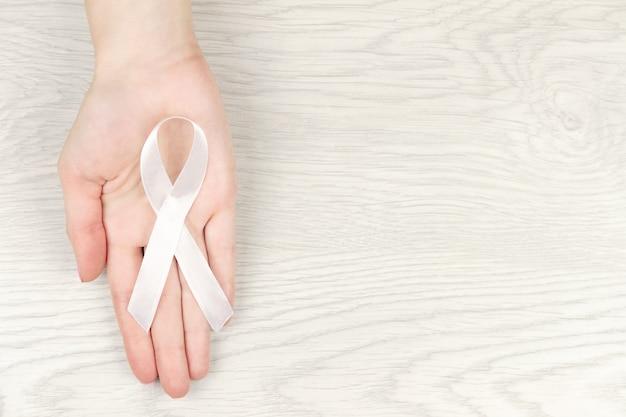 Conceito de doença oncológica. mão segurando a fita branca como um símbolo de câncer de pulmão Foto Premium