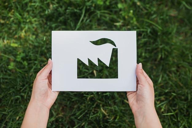 Conceito de eco com as mãos segurando papel cortado mostrando fábrica Foto Premium