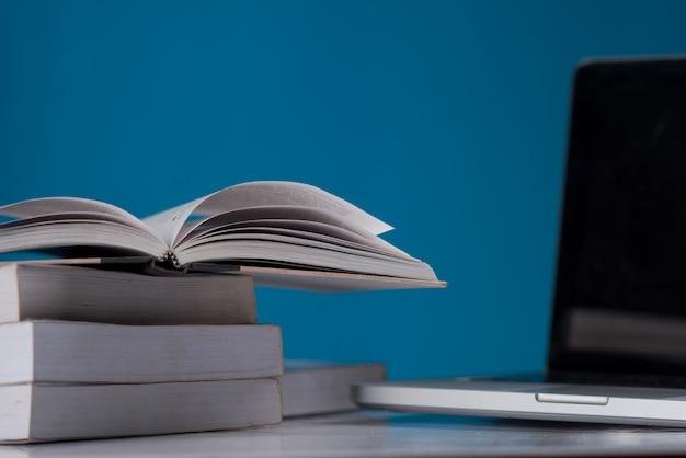 Conceito de educação, livros e laptop na biblioteca Foto gratuita