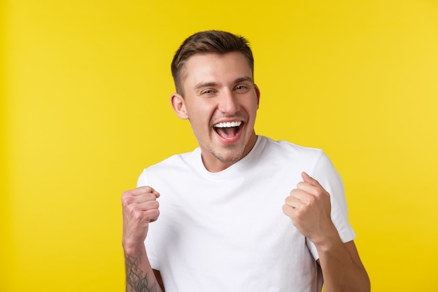 Conceito de emoções de estilo de vida, verão e pessoas. retrato do close-up de regozijando-se bonito feliz pulando de alegria, ganhando na loteria ou prêmio, cantando e rindo sobre o sucesso. Foto gratuita