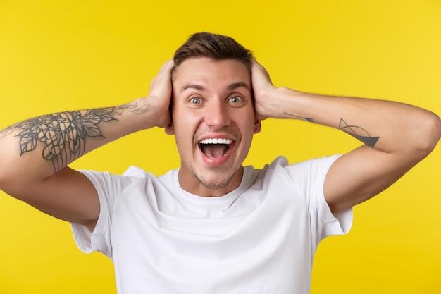 Conceito de emoções de estilo de vida, verão e pessoas. retrato do close-up de um jovem regozijando-se extremamente feliz parecendo surpreso, não posso acreditar que ele ganhou o prêmio, mãos na cabeça em negação, fundo amarelo. Foto gratuita