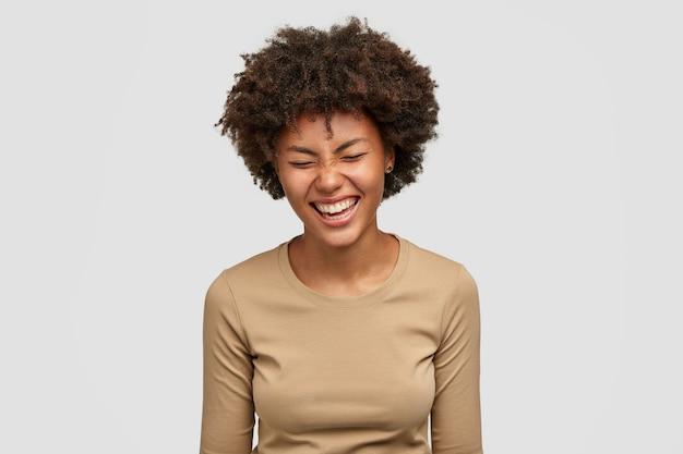 Conceito de emoções humanas positivas. feliz encaracolada jovem afro-americana com expressão alegre, risos e risos de algo engraçado, aperta os olhos de felicidade, isolada sobre uma parede branca Foto gratuita