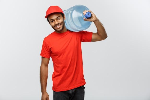 Conceito de entrega - handsome african american delivery man segurando tanque de água. isolado no fundo do estúdio cinzento. espaço de cópia. Foto gratuita