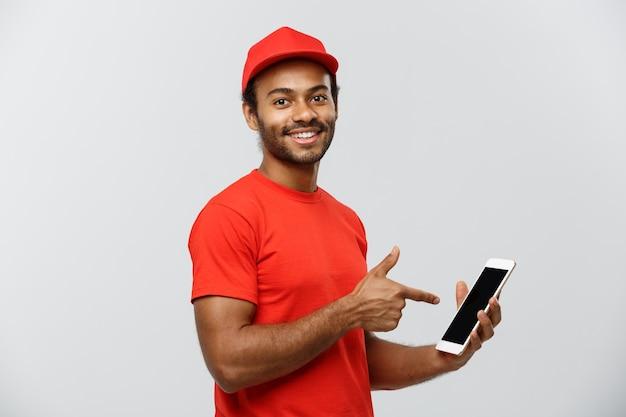 Conceito de entrega - retrato de handsome african american delivery man ou courier com caixa mostrando tablet em você para verificar a ordem. isolado no fundo do estúdio cinzento. espaço de cópia. Foto gratuita