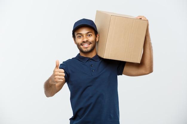 Conceito de entrega - retrato do homem de entrega feliz africano-americano em pano vermelho, segurando um pacote de caixa. isolado no fundo do estúdio cinzento. espaço de cópia. Foto gratuita