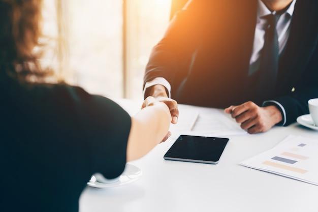 Conceito de entrevista de negócios - empresário e mulher fazendo aperto de mão no escritório Foto Premium