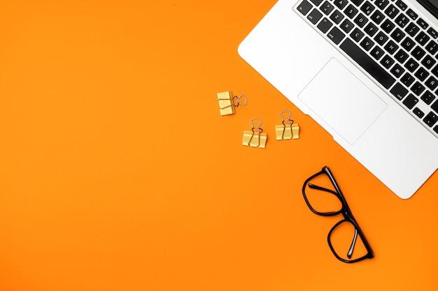 Conceito de espaço de trabalho de vista superior com fundo laranja Foto gratuita