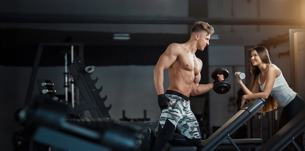 Conceito de esporte, treinamento, fitness, estilo de vida e as pessoas - jovem com personal trainer, flexionando os músculos traseiros e abdominais no banco no ginásio Foto Premium