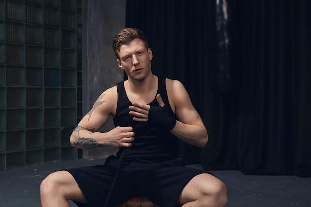 Conceito de esportes e artes marciais. retrato de jovem bonito em forma de homem com tatuagens nos braços, sentado dentro de casa e amarrando bandagens de boxe no pulso, preparando-se para o treinamento, com olhar confiante Foto gratuita