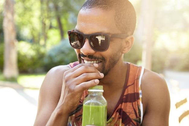 Conceito de estilo de vida de rua. jovem sorridente homem afro-americano com bigode e barba curta bebendo suco fresco durante o encontro, vestido casualmente em regata colorida e tons da moda ou óculos de sol Foto gratuita