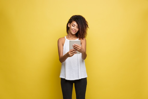Conceito de estilo de vida - retrato da bela mulher afro-americana alegre jogando algo no tablet eletrônico. fundo de estúdio amarelo pastel. espaço de cópia. Foto gratuita