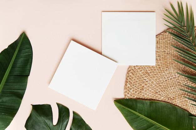 Conceito de estilo flatlay, folha de papel branco e folhas de palmeira tropical na parede rosa Foto Premium