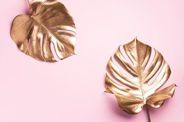 Conceito de estilo minimalista floral. tendência exótica de verão. folha de palmeira tropical dourada monstera Foto Premium