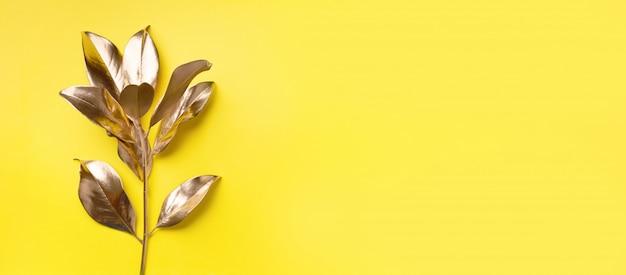 Conceito de estilo minimalista floral. tendência exótica de verão. ramo e folhas tropicais douradas Foto Premium