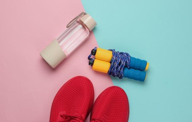 Conceito de estilo plano leigo de estilo de vida saudável, esporte e fitness. tênis para corrida, garrafa de água, pular corda em fundo rosa pastel azul. vista do topo Foto Premium