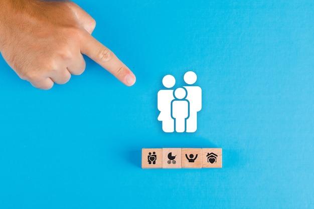 Conceito de família com bloco de madeira, ícone de família de papel na mesa plana azul leigos. mão apontando do homem. Foto gratuita