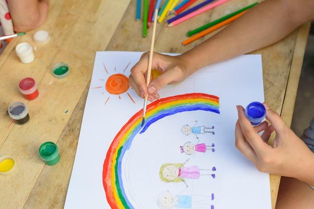Conceito de família feliz. criança desenha em uma folha de papel: pai, mãe, menino e menina de mãos dadas Foto Premium