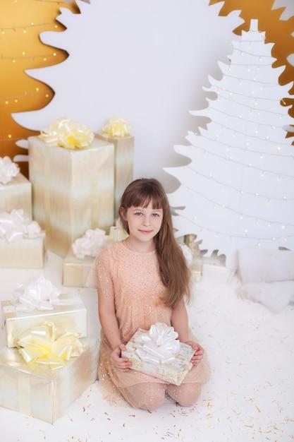 Conceito de férias de natal. menina de vestido dourado, sentado junto à árvore de natal com presente. Foto Premium