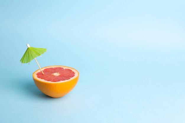Conceito de férias de verão. toranja com um guarda-chuva de cocktail em um fundo colorido. trópicos, sol, praia, vitaminas, frutas, verão e bom humor Foto Premium